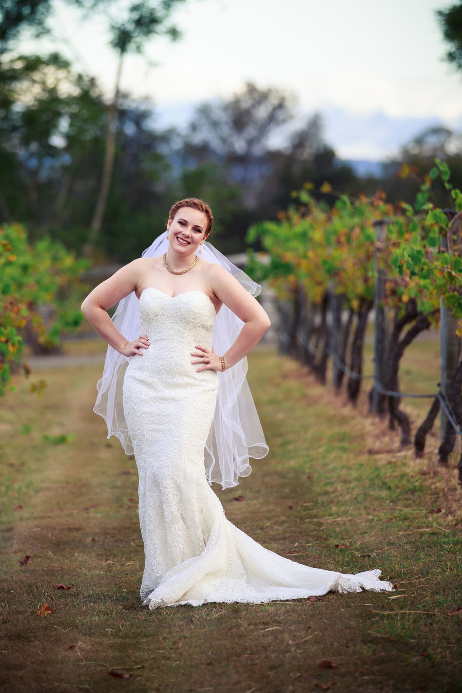 photo of Jes the bride between grape vines with hands on hips.