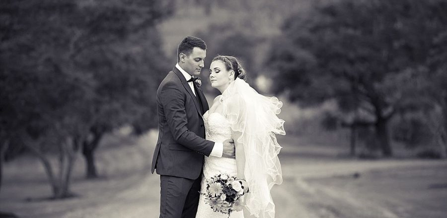 Black and white image of bride and groom embracing with eyes shut