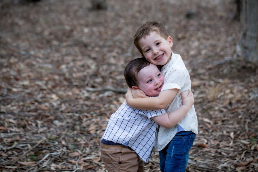 A photo of two young brothers hugging.