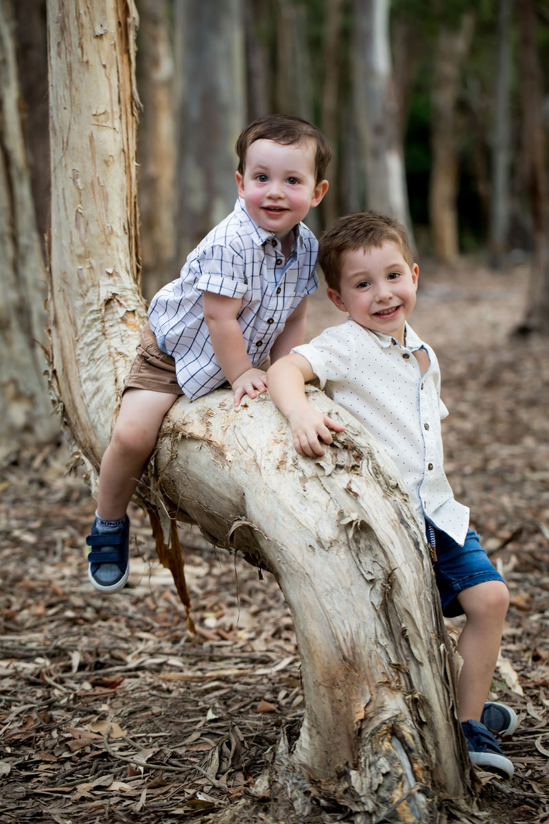 image of two brothers, one sitting on the tree the other leaning