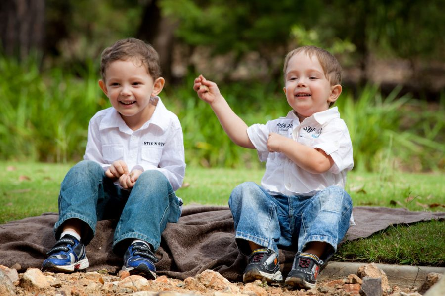 image of two young brothers sitting and throwing stones