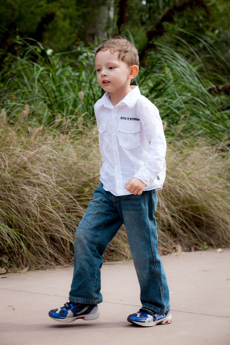 image of young boy walking along a path side on