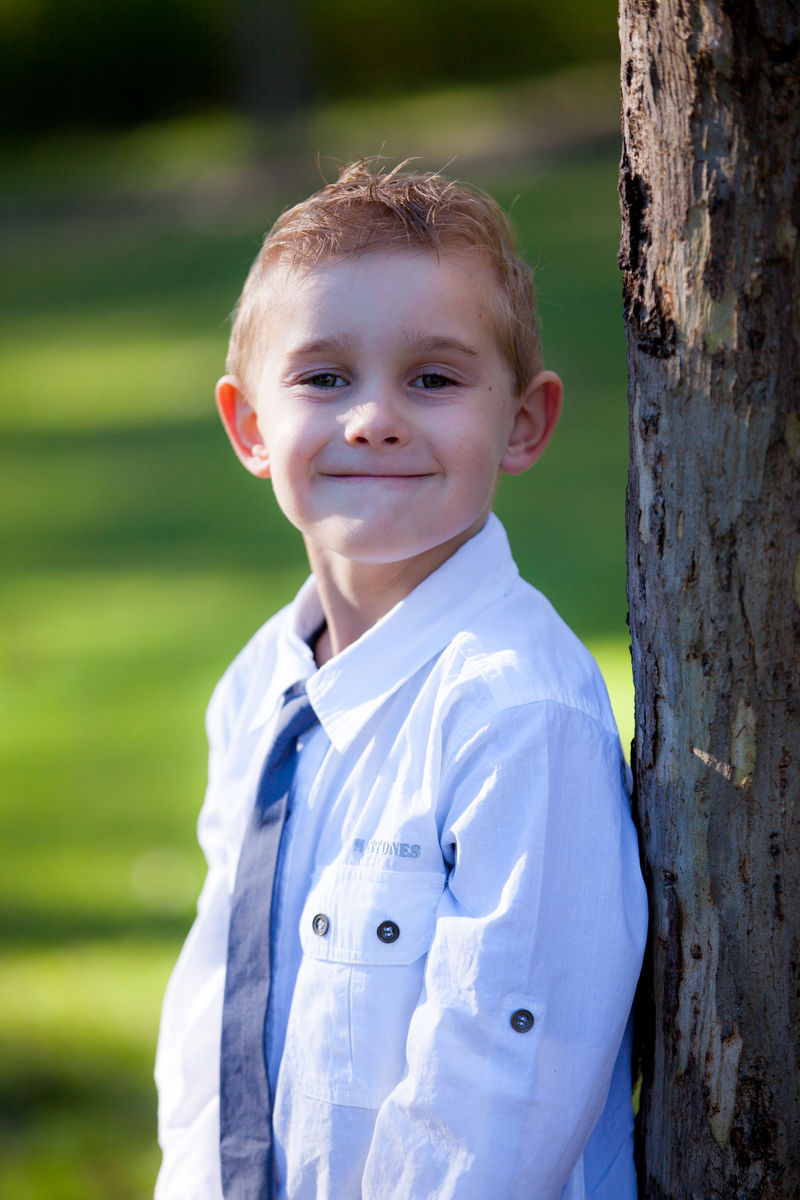 image of young boy with a smile leaning on a tree