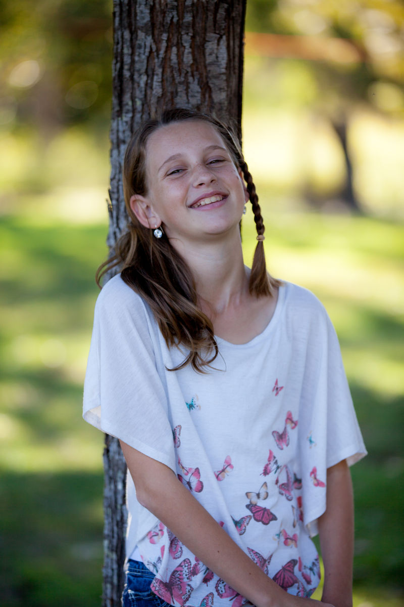 image of smiling teenage girl leaning against tree